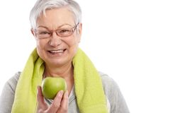 Gesunde alte Frau mit dem grünen Apfellächeln Stockfoto