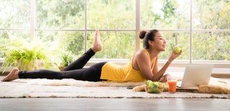Gesunde Asiatin, die auf dem Boden isst den Salat schaut entspannt und bequem liegt stockfotos