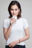 Gesunde Asiatin, die ein Glas Milch trinkt Stockfotografie