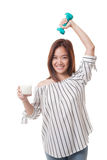 Gesunde Asiatin, die ein Glas von Milch und von Dummkopf trinkt Stockfoto