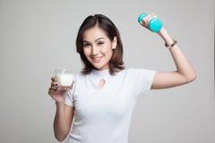 Gesunde Asiatin, die ein Glas von Milch und von Dummkopf trinkt Lizenzfreie Stockfotografie