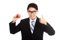 Gesunde asiatische Geschäftsmanndaumen oben mit rotem Apfel Stockfotografie