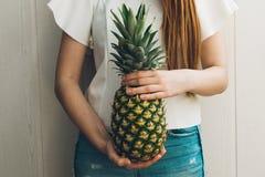 Gesunde dünne Frau, die eine Ananas hält Sommerdi?tkonzept lizenzfreies stockbild