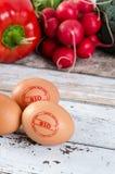 Gesunde Eier mit BIOstempel Gemüse im Hintergrund Lizenzfreies Stockfoto