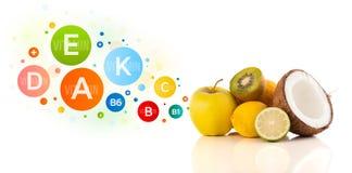 Gesunde Früchte mit bunten Vitaminsymbolen und -ikonen Lizenzfreie Stockfotografie
