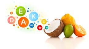 Gesunde Früchte mit bunten Vitaminsymbolen und -ikonen Stockfoto