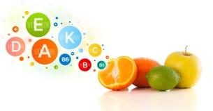 Gesunde Früchte mit bunten Vitaminsymbolen und -ikonen Stockfotografie