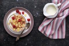 Gesunde FrühstücksCorn Flakes mit Himbeeren u. Milch auf dunklem ta Lizenzfreie Stockfotografie