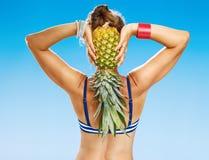 Gesunde Frau in der Strandkleidung auf dem Strand, der Ananas hält Lizenzfreies Stockfoto