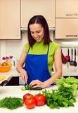 Gesunde Frau des smiley, die einen Salat zubereitet Stockfotografie