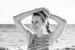 Gesunde Frau, die Abstand untersucht und Musik hört Lizenzfreie Stockfotografie