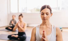 Gesunde Frau, die das Meditieren in der Yogaklasse tut stockfotografie