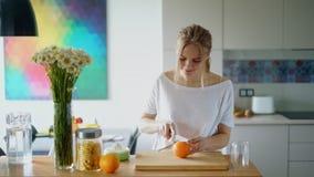 Gesunde Frau, die Orange auf hölzernem Brett schneidet Zubereitung des Morgenfrühstücks stock video