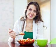 Gesunde Frau, die Veggiesalat mit Löffel isst stockbilder
