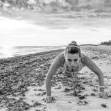 Gesunde Frau im Sport kleidet auf dem Strand, der Liegestütze tut Stockfoto