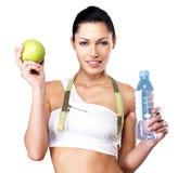 Gesunde Frau mit Apfel und Flasche Wasser Stockfoto