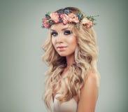 Gesunde Frau mit Blumen, blonde gelockte Frisur Lizenzfreie Stockbilder