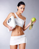 Gesunde Frau mit den Skalen und dem grünen Apfel. Lizenzfreie Stockbilder