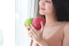 Gesunde Frau nett, grünen und roten Apfel essend stockbild