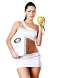Gesunde Frau steht mit den Skalen und dem grünen Apfel. Stockbild