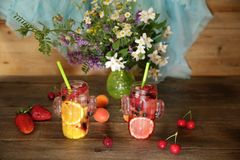 Gesunde frische Früchte und Beeren Smoothies in den Glasflaschen mit Strohen auf einem rustikalen Holztisch verziert mit Blumen u stockbilder