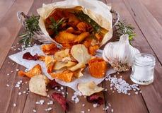 Gesunde Gemüsechips auf Papier mit Seesalz, -rosmarin und -knoblauch Stockfotografie