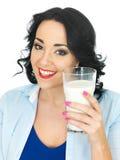 Gesunde glückliche Frau, die ein großes Glas frische Milch hält Stockfoto