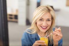 Gesunde glückliche Frau, die Orangensaft trinkt Stockfotos