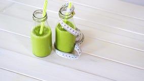 Gesunde Grün- und Vegetariercocktails mit Zentimeterband auf weißem Holztisch stock video