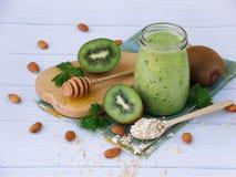 Gesunde grüne Smoothies von der Kiwi, vom Hafermehl, von den Nüssen und vom Honig auf hellem Hintergrund Lizenzfreie Stockfotografie