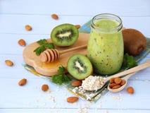 Gesunde grüne Smoothies von der Kiwi, vom Hafermehl, von den Nüssen und vom Honig auf hellem Hintergrund Lizenzfreies Stockfoto