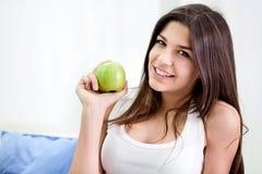 Gesunde Jugendliche, die einen grünen Apfel anhält stockbild