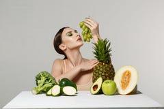 Gesunde junge brunette Frau, die grüne Trauben in ihrer Hand betrachtet stockbild