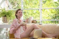 Gesunde junge Frau, die auf einer Couch hält eine Schüssel Jogurt schauend entspannt und bequem liegt stockfotos