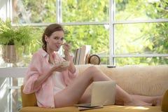 Gesunde junge Frau, die auf einer Couch isst den Jogurt schaut entspannt und bequem liegt stockfoto