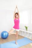 Gesunde junge Frau, die zu Hause Yoga tut Stockfotos