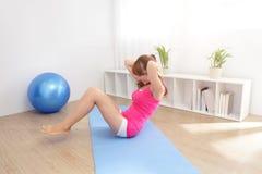 Gesunde junge Frau, die zu Hause Yoga tut Stockbilder