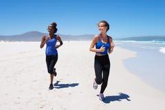 Gesunde junge Frauen, die entlang den Strand laufen Lizenzfreies Stockfoto