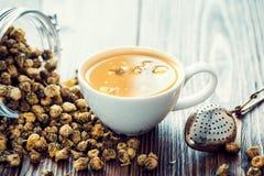 Gesunde Kamillenteeschale, -sieb und -Glasgefäß mit trockenem Gänseblümchen Stockfoto
