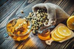 Gesunde Kamillenteeschale, Tasche des groben Sackzeugs von trockenen Gänseblümchenblumen, Honigglas und Zitronenscheiben Lizenzfreie Stockbilder