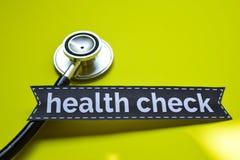 Gesunde Kontrolle der Nahaufnahme mit Stethoskopkonzeptinspiration auf gelbem Hintergrund stockbild