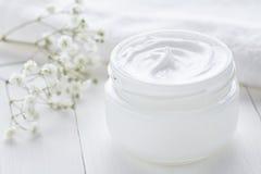 Gesunde kosmetische Creme mit Kräuterblumen stellen Sorgfalthygienefeuchtigkeit gegenüber Stockfoto