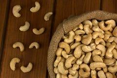 Gesunde Lebensmittel Acajounuss in der Sacktasche auf hölzernem Tabellenhintergrund Stockfotografie