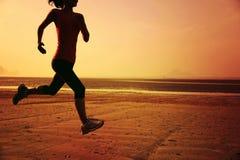 Gesunde Lebensstilfrau, die am Sonnenaufgangstrand läuft Stockfoto