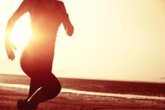 Gesunde Lebensstilfrau, die am Sonnenaufgangstrand läuft Lizenzfreies Stockfoto