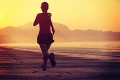 Gesunde Lebensstilfrau, die am Sonnenaufgangstrand läuft Stockbilder