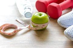 Gesunde Lebensstilsportausrüstungseignung, Turnschuhe, grüner Apfel, Süßwasser und gesundes Lebensmittel auf Purplehearthintergru Lizenzfreie Stockfotografie