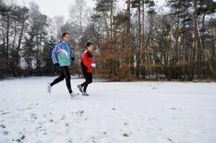 Gesunde Leute, die in den Schnee laufen lizenzfreie stockfotos