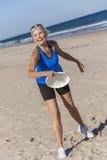 Gesunde ältere Frau, die Frisbee am Strand spielt Stockbild