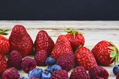 Gesunde Mischfrucht und Bestandteile mit Erdbeere, Himbeere, Blaubeere Beeren auf rustikalem weißem hölzernem Hintergrund Stockfotografie